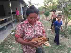 鶏を大事そうに抱える孤児院のママ