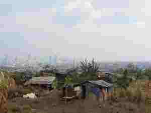 遠くには高層ビル、近くには貧困層の家が見えています。